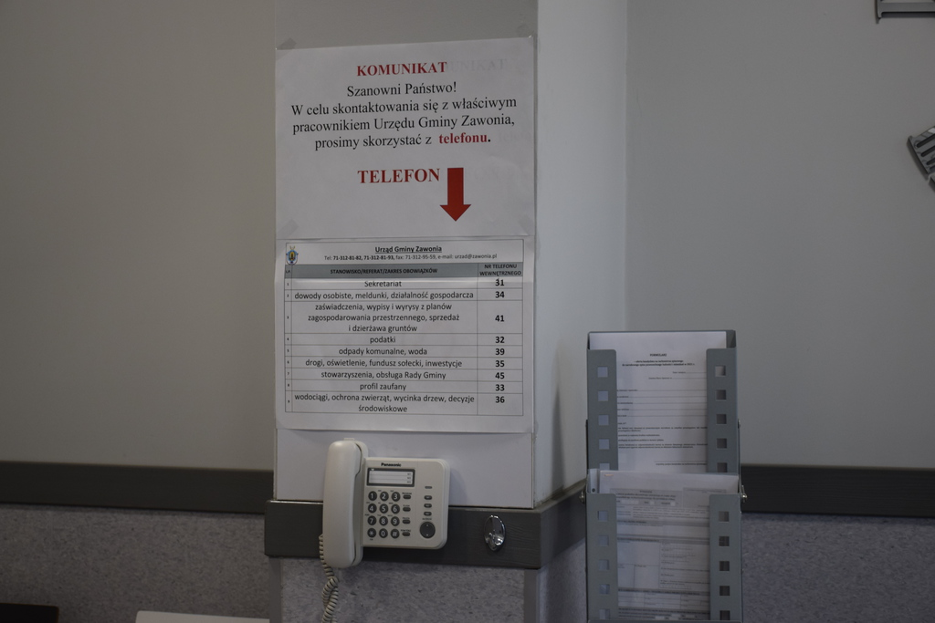 Na ścianie zamontowany jest telefon wewnętrzny za pomocą, którego można połączyć się z dowolnym pracownikiem urzędu. Nad telefonem umieszczona jest kartka z numerami telefonów.