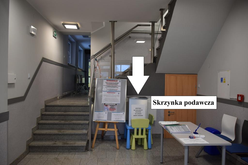 Biała strzałka wskazuje, gdzie znajduje się skrzynka podawcza w holu urzędu.
